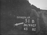 SD990751B, Man marking Ordnance Survey minor control revision point with an arrow in 1950s