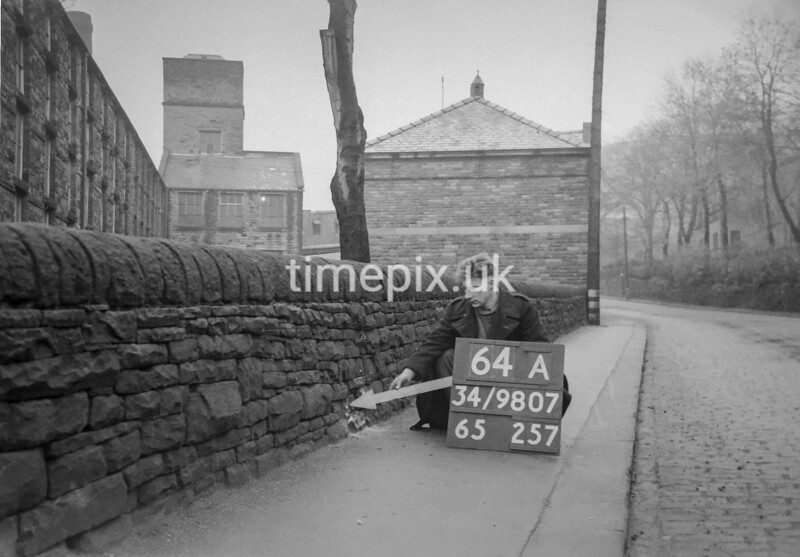 SD980764A, Man marking Ordnance Survey minor control revision point with an arrow in 1950s