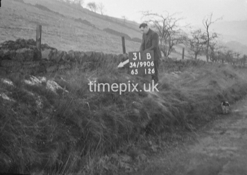 SD990631B, Man marking Ordnance Survey minor control revision point with an arrow in 1950s