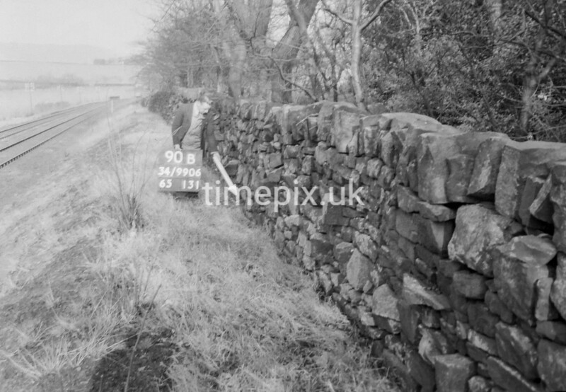 SD990690B, Man marking Ordnance Survey minor control revision point with an arrow in 1950s