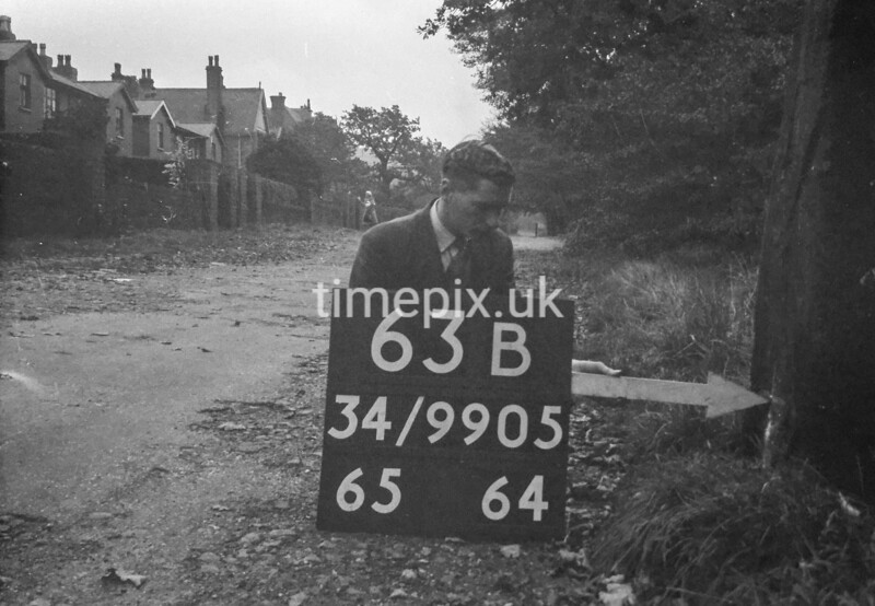 SD990563B, Man marking Ordnance Survey minor control revision point with an arrow in 1950s