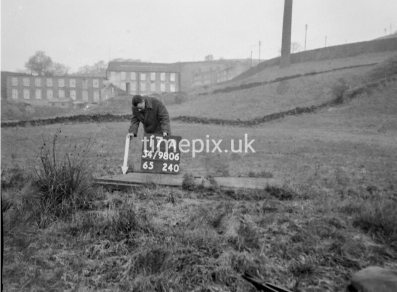 SD980617A, Man marking Ordnance Survey minor control revision point with an arrow in 1950s