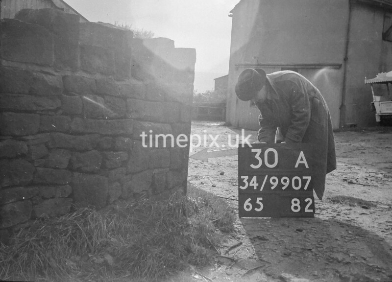 SD990730A, Man marking Ordnance Survey minor control revision point with an arrow in 1950s
