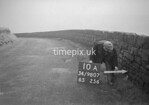 SD980710A, Man marking Ordnance Survey minor control revision point with an arrow in 1950s