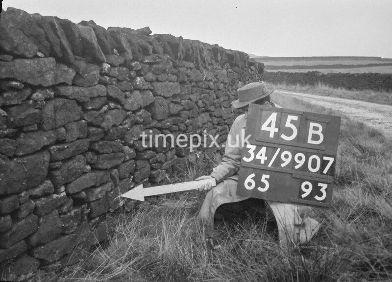 SD990745B, Man marking Ordnance Survey minor control revision point with an arrow in 1950s