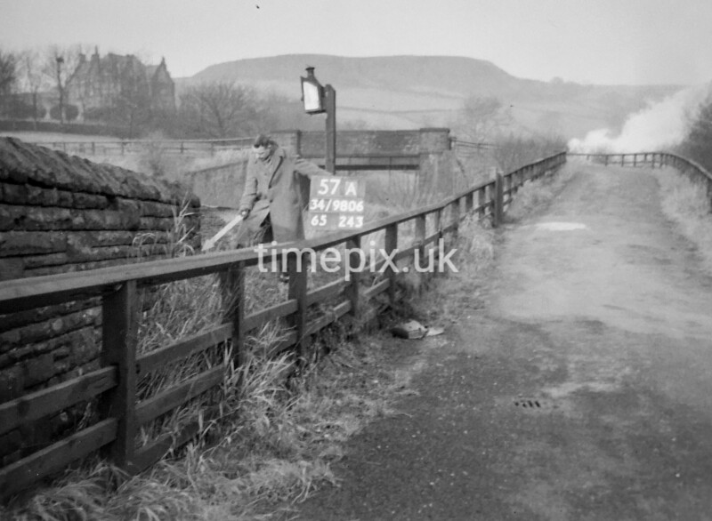 SD980657A, Man marking Ordnance Survey minor control revision point with an arrow in 1950s