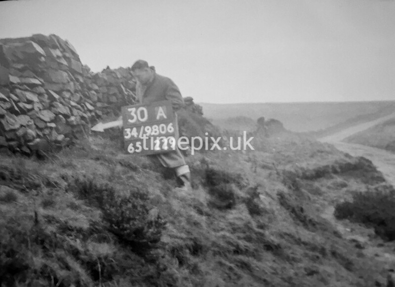 SD980630A, Man marking Ordnance Survey minor control revision point with an arrow in 1950s