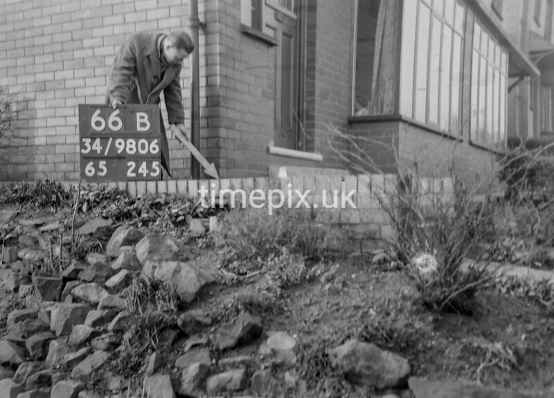 SD980666B, Man marking Ordnance Survey minor control revision point with an arrow in 1950s