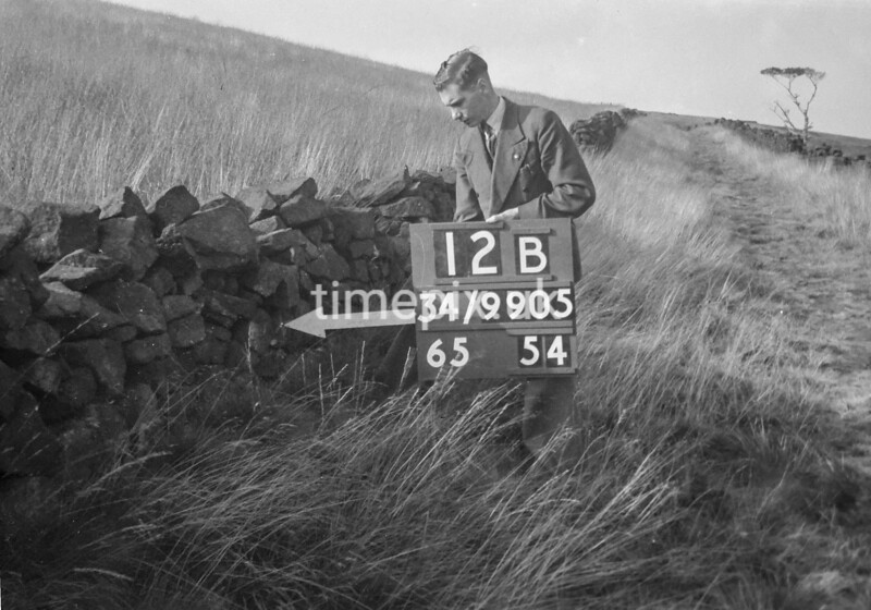 SD990512B, Man marking Ordnance Survey minor control revision point with an arrow in 1950s