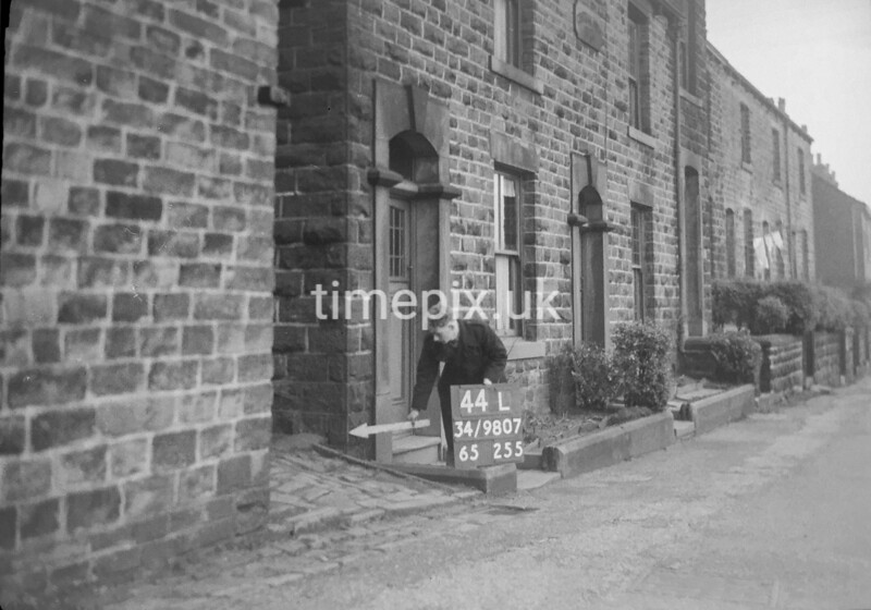 SD980744L, Man marking Ordnance Survey minor control revision point with an arrow in 1950s