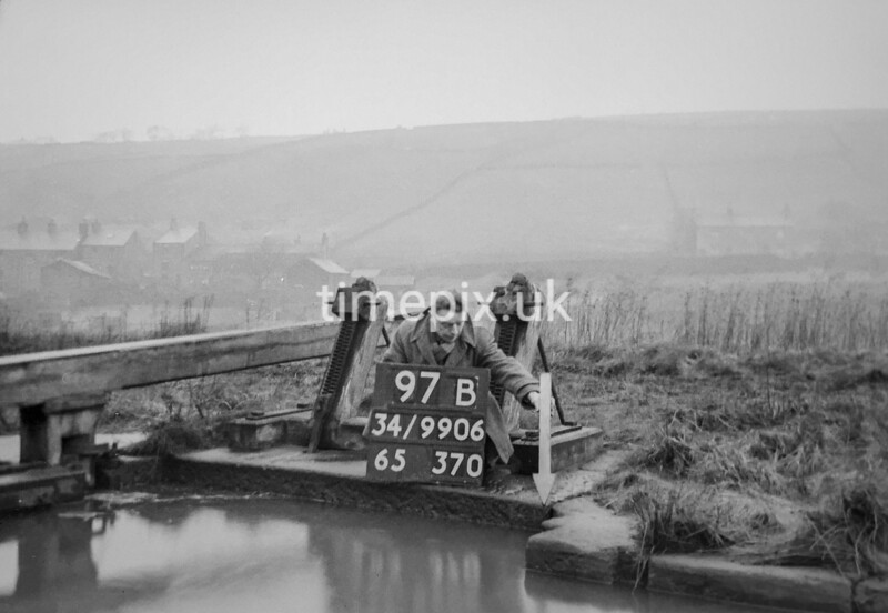 SD990697B2, Man marking Ordnance Survey minor control revision point with an arrow in 1950s