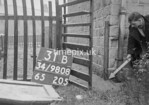 SD980831B, Man marking Ordnance Survey minor control revision point with an arrow in 1950s
