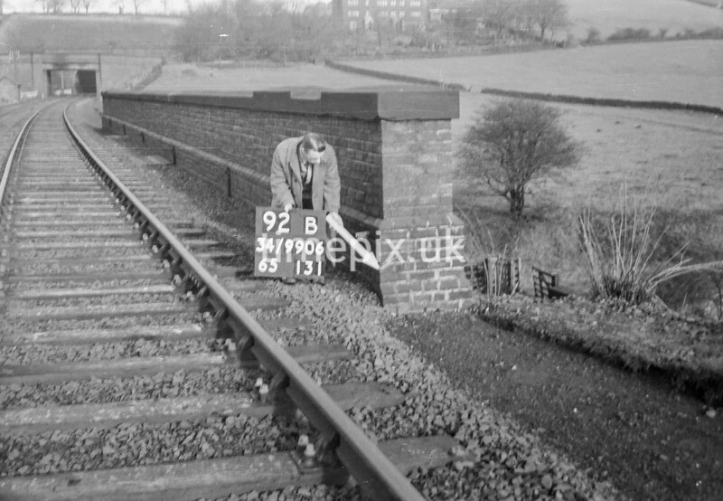 SD990692B, Man marking Ordnance Survey minor control revision point with an arrow in 1950s