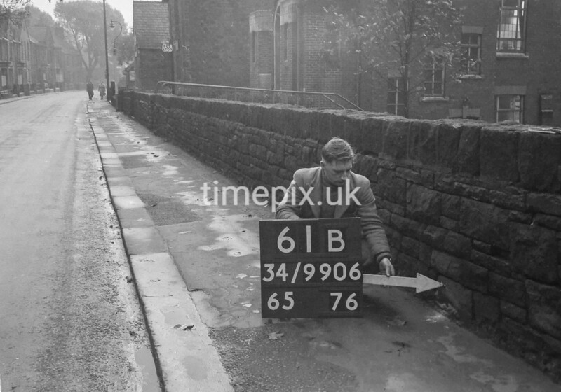 SD990661B, Man marking Ordnance Survey minor control revision point with an arrow in 1950s