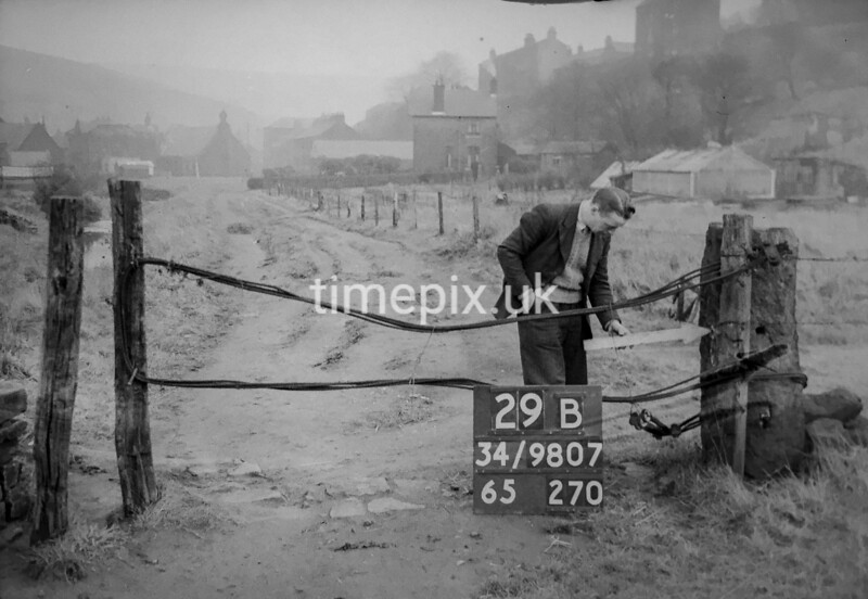 SD980729B, Man marking Ordnance Survey minor control revision point with an arrow in 1950s