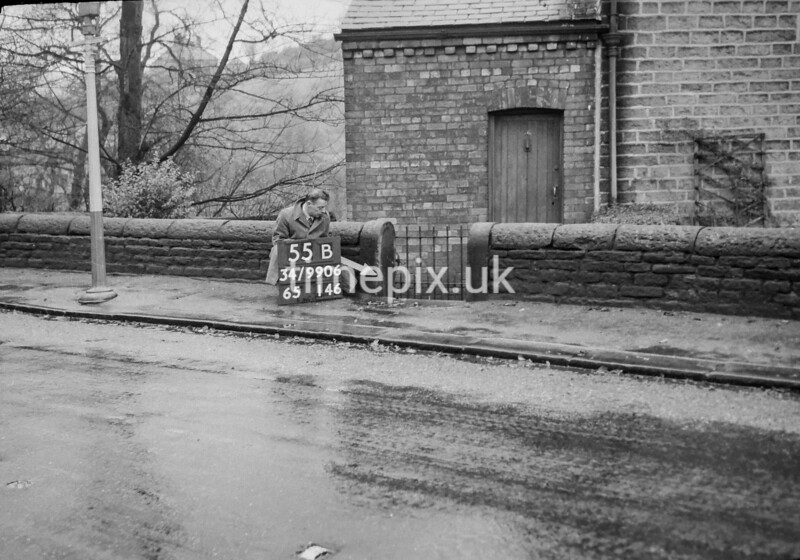 SD990655B, Man marking Ordnance Survey minor control revision point with an arrow in 1950s