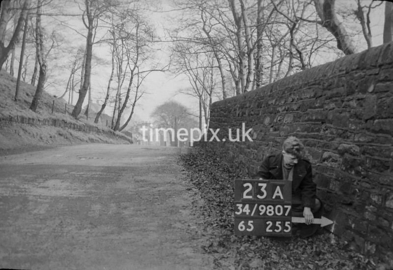 SD980723A, Man marking Ordnance Survey minor control revision point with an arrow in 1950s