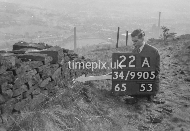 SD990522A, Man marking Ordnance Survey minor control revision point with an arrow in 1950s