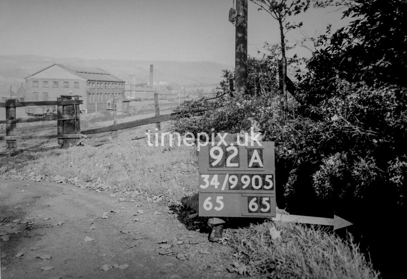 SD990592A, Man marking Ordnance Survey minor control revision point with an arrow in 1950s