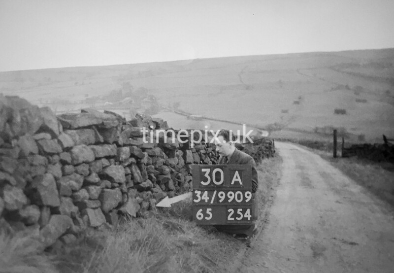 SD990930A, Man marking Ordnance Survey minor control revision point with an arrow in 1950s