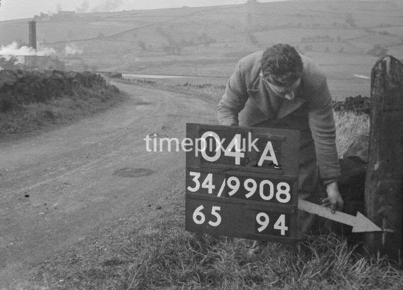 SD980804A, Man marking Ordnance Survey minor control revision point with an arrow in 1950s