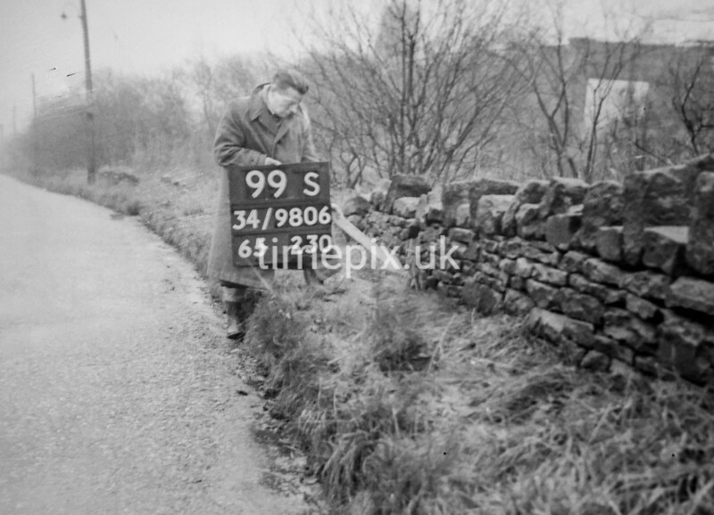 SD980699S, Man marking Ordnance Survey minor control revision point with an arrow in 1950s
