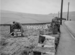 SD980629A, Man marking Ordnance Survey minor control revision point with an arrow in 1950s