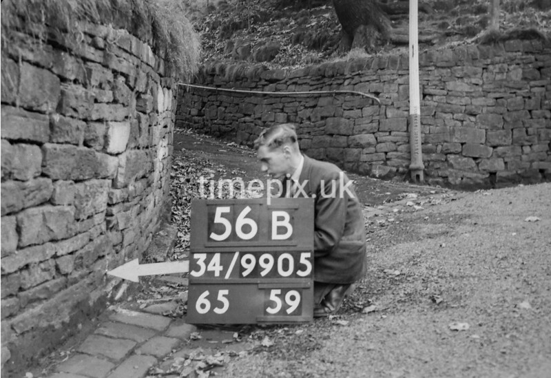 SD990556B, Man marking Ordnance Survey minor control revision point with an arrow in 1950s