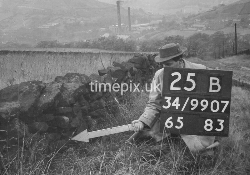 SD990725B, Man marking Ordnance Survey minor control revision point with an arrow in 1950s