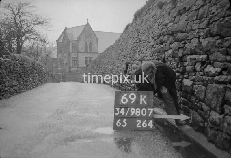 SD980769K, Man marking Ordnance Survey minor control revision point with an arrow in 1950s