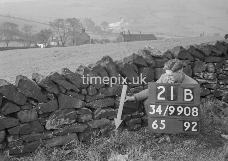SD990821B, Man marking Ordnance Survey minor control revision point with an arrow in 1950s