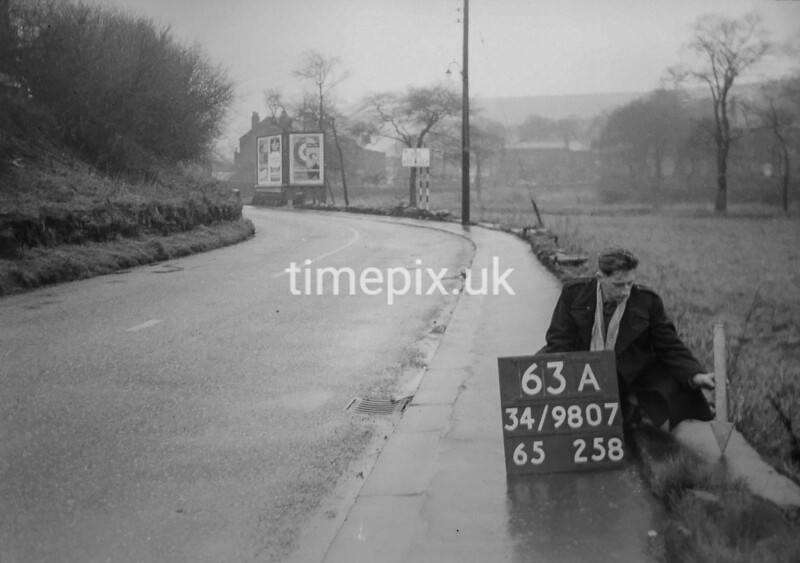 SD980763A, Man marking Ordnance Survey minor control revision point with an arrow in 1950s