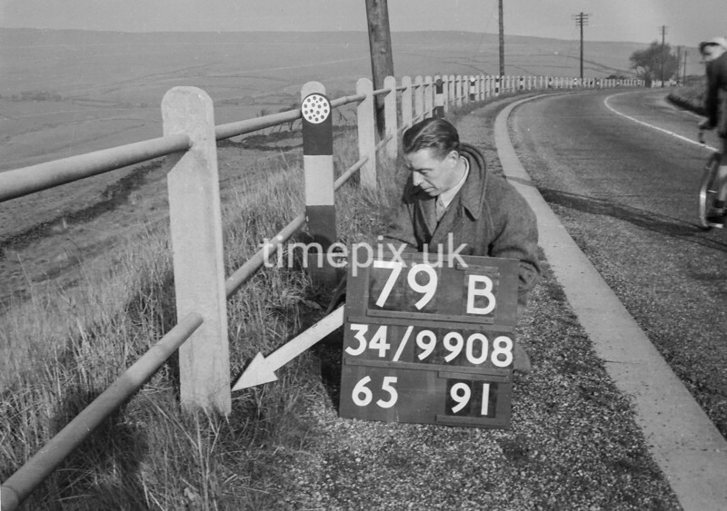 SD990879B, Man marking Ordnance Survey minor control revision point with an arrow in 1950s