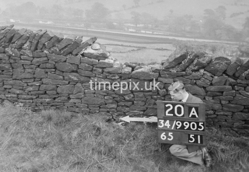 SD990520A, Man marking Ordnance Survey minor control revision point with an arrow in 1950s