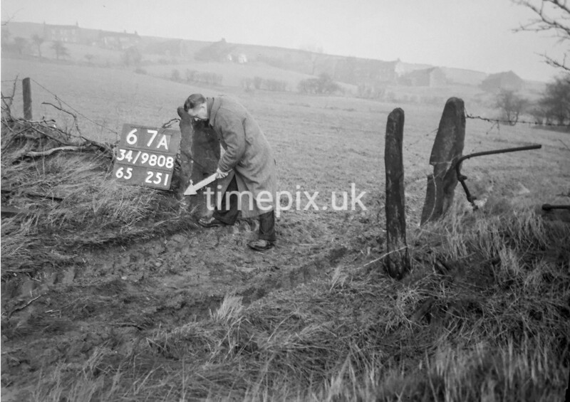 SD980867A, Man marking Ordnance Survey minor control revision point with an arrow in 1950s