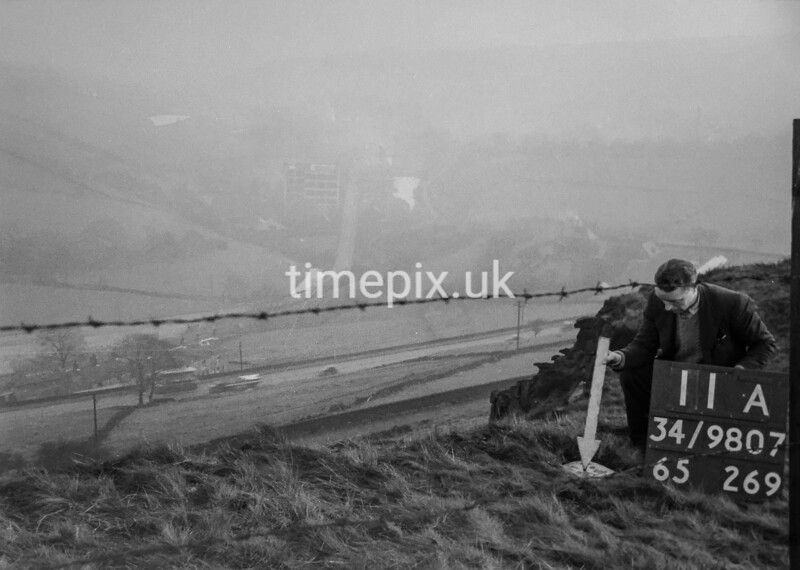 SD980711A, Man marking Ordnance Survey minor control revision point with an arrow in 1950s