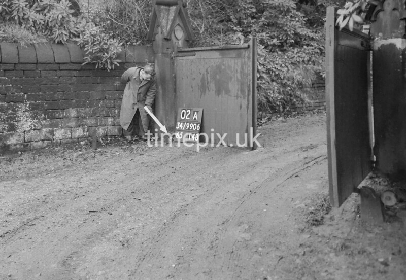 SD990602A2, Man marking Ordnance Survey minor control revision point with an arrow in 1950s