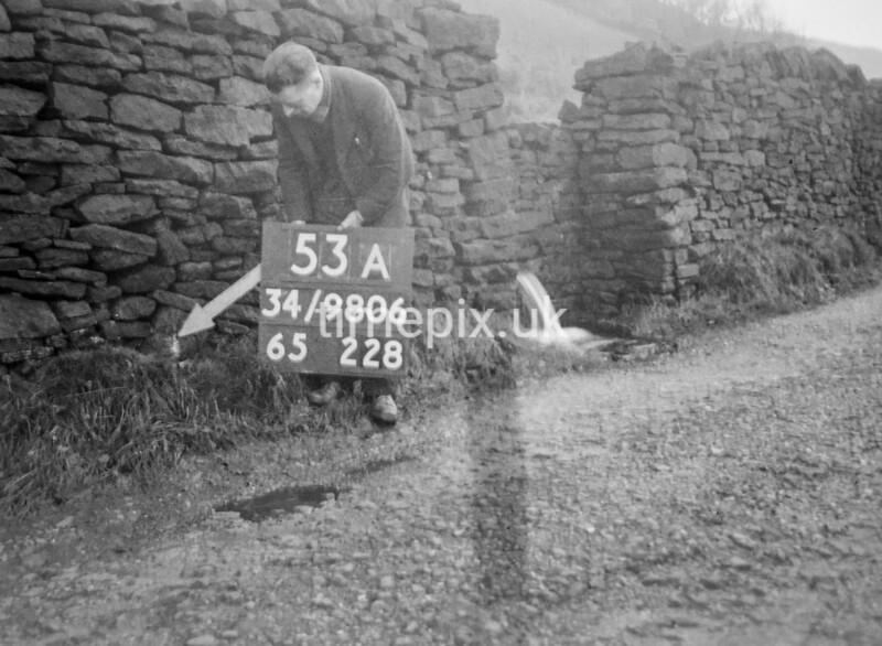 SD980653A, Man marking Ordnance Survey minor control revision point with an arrow in 1950s