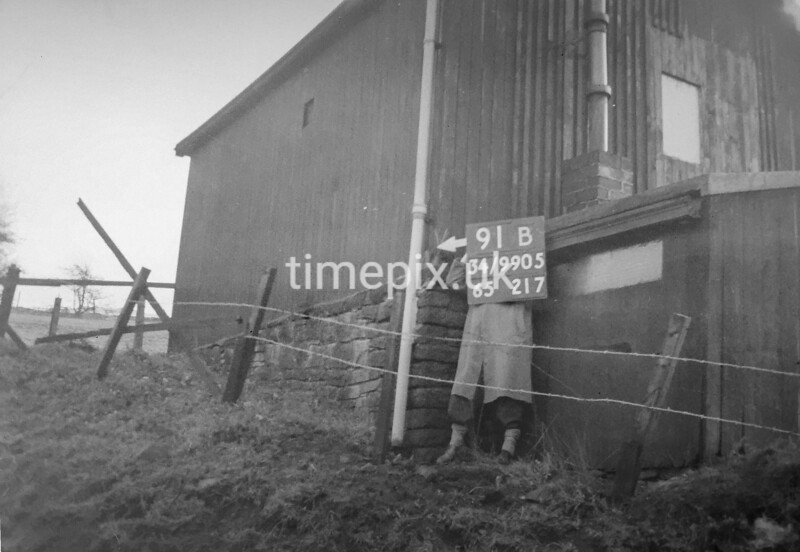 SD990591B, Man marking Ordnance Survey minor control revision point with an arrow in 1950s