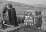 SD990807A, Man marking Ordnance Survey minor control revision point with an arrow in 1950s