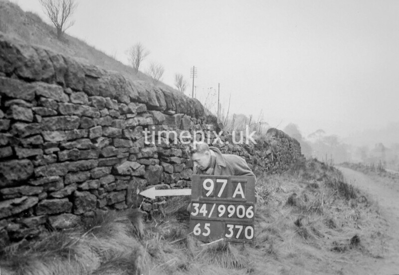 SD990697A3, Man marking Ordnance Survey minor control revision point with an arrow in 1950s
