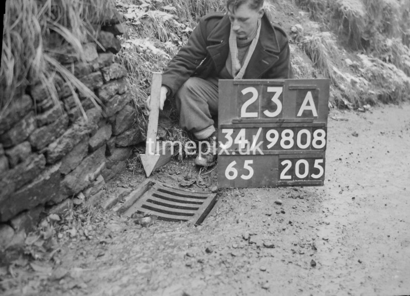 SD980823A, Man marking Ordnance Survey minor control revision point with an arrow in 1950s