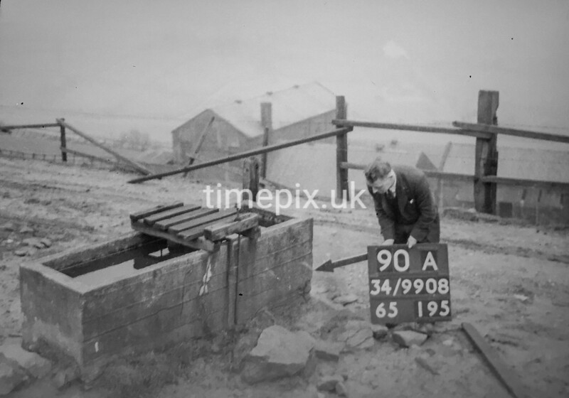 SD990890A, Man marking Ordnance Survey minor control revision point with an arrow in 1950s