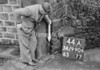 SD990644A, Man marking Ordnance Survey minor control revision point with an arrow in 1950s