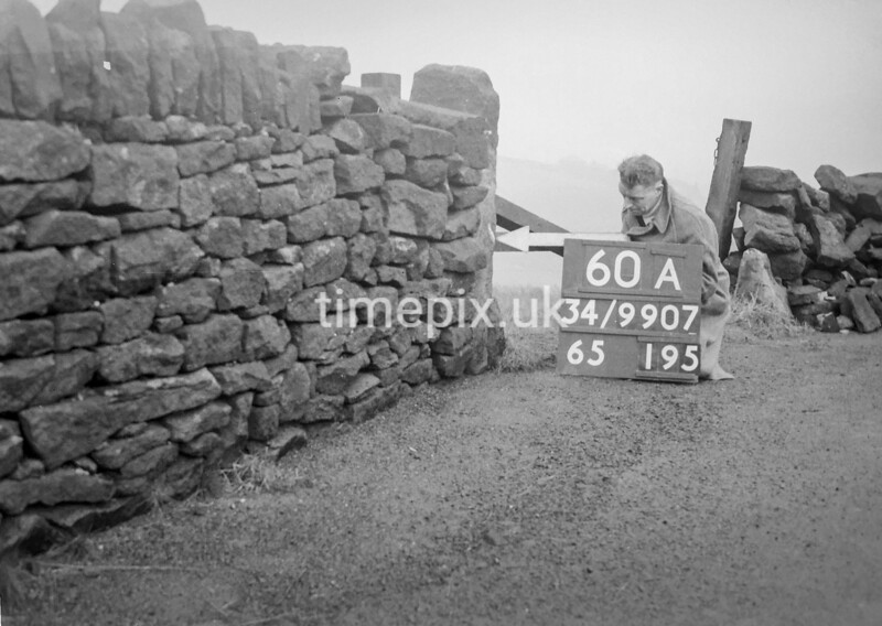 SD990760A2, Man marking Ordnance Survey minor control revision point with an arrow in 1950s