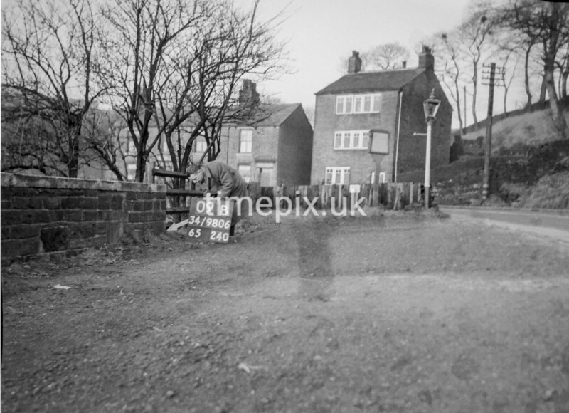 SD980609B, Man marking Ordnance Survey minor control revision point with an arrow in 1950s