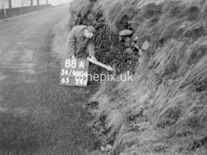 SD980688A, Man marking Ordnance Survey minor control revision point with an arrow in 1950s