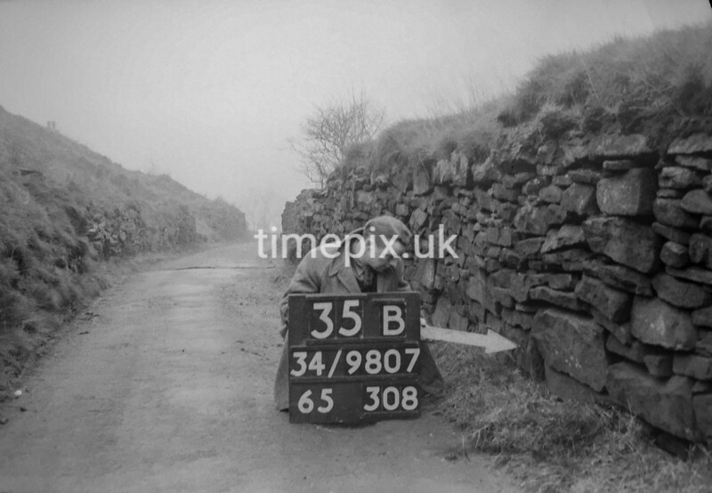 SD980735B, Man marking Ordnance Survey minor control revision point with an arrow in 1950s