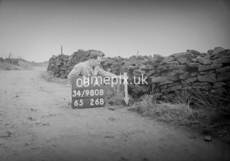 SD980808A, Man marking Ordnance Survey minor control revision point with an arrow in 1950s