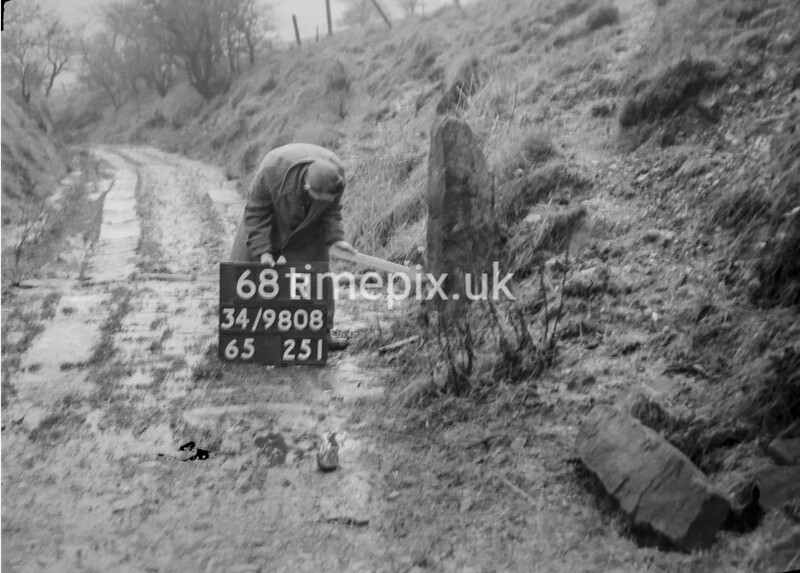 SD980868R, Man marking Ordnance Survey minor control revision point with an arrow in 1950s
